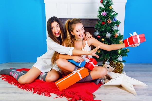 Gemütliches, helles widerrist-urlaubsporträt von zwei hübschen schwestern der besten freunde, die in der nähe des kamins sitzen und den weihnachtsbaum schmücken und geschenke von ihrer familie halten. positive emotionen und stimmung.