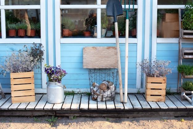 Gemütliches herbstdekor-veranda-haus. holzveranda des hauses mit pflanzen, protokollen.