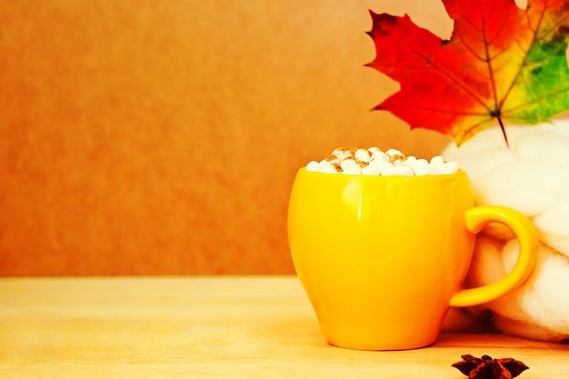Gemütliches herbstkonzept mit gelber tasse kakao mit marshmallow und zimt