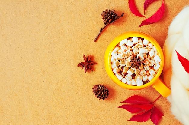 Gemütliches herbstkonzept mit gelber tasse kakao mit marshmallow