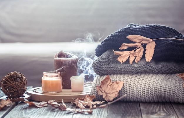 Gemütliches herbststillleben mit kerzen und pullover