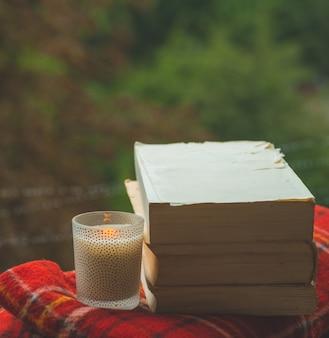 Gemütliches herbststillleben: tasse heißen kaffee und geöffnetes buch auf vintage-fensterbank mit roter decke, kürbis, tannenzapfen, kerzen und regen draußen. herbst. wohnung. regen