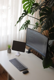Gemütliches homeoffice für entwickler mit gebogenem bildschirm und tablet. komfortarbeit zu hause