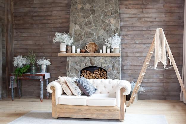 Gemütliches innenwohnzimmer weißes sofa und kamin. rustikales wohndesign für warme innenraum-alpenferien. moderner häuschen-wohnzimmer-dekor mit hölzerner wand und möbeln. skandinavischer stil. boho