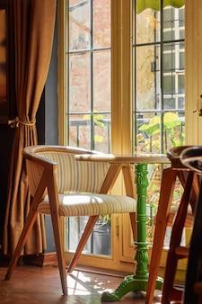 Gemütliches interesse, ein sessel und ein runder tisch mit einem grünen stiel neben dem großen fenster