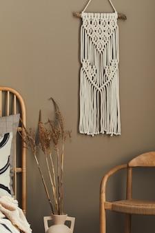 Gemütliches interieur des stilvollen schlafzimmers mit designdekoration, neutralem makramee, getrockneten blumen in vase, stuhl, schöner bettwäsche, decke, kissen und persönlichen accessoires