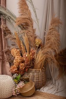 Gemütliches interieur des zimmers in brauntönen mit getrockneten blumen, pampasgras und zweigen im korb. trockene blumen im topf im eleganten rauminnenraum mit natürlichen akzenten