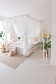 Gemütliches interieur eines hellen apartments im balinesischen stil mit weißen wänden und bambusmöbeln. schlafzimmer mit nachtlichtern, bett mit balanchin und großen fenstern