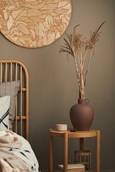 Gemütliches interieur eines stilvollen schlafzimmers mit designdekoration, nachttisch aus holz, keramikgefäß, buch, getrockneten blumen in der vase, schönen bettlaken, decke, kissen und persönlichem zubehör.