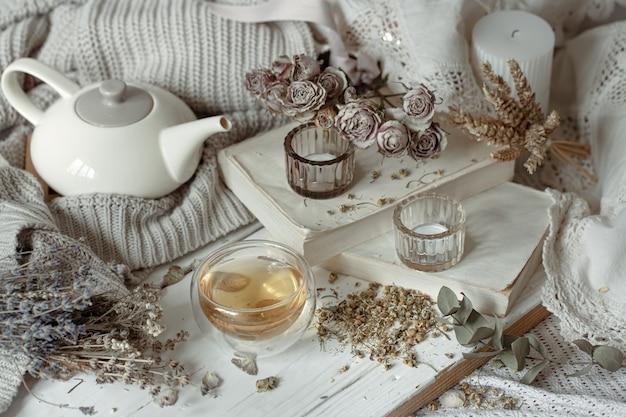 Gemütliches lichtstillleben mit kerzen, einer tasse tee, einer teekanne und trockenen kräutern.