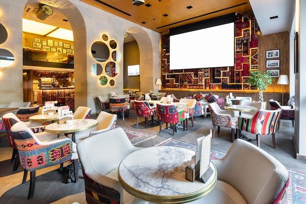 Gemütliches modernes interieur des restaurants, teehaus mit weißer projektionswand