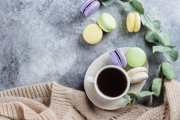 Gemütliches morgen-konzept. köstliche bunte pastell-macarons mit sahne und kaffee, warme graue strickjacke