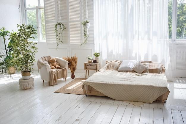 Gemütliches schlafzimmer des stilvollen dachbodens mit doppelbett, lehnsessel