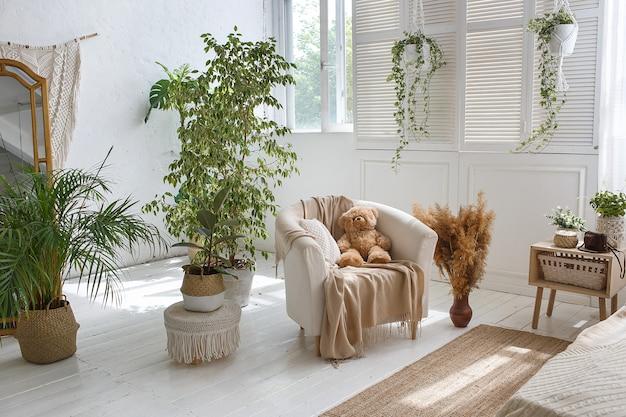 Gemütliches schlafzimmer des stilvollen dachbodens mit lehnsessel und teddybären