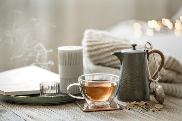Gemütliches stillleben mit einer glastasse tee, einer teekanne und kerzen auf unscharfem hintergrund mit bokeh.