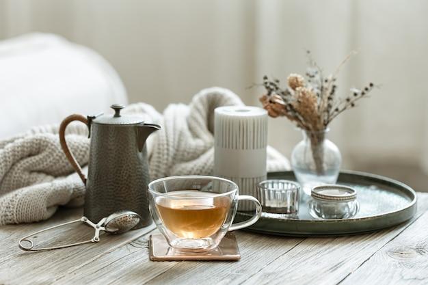 Gemütliches stillleben mit einer glastasse tee, einer teekanne und kerzen auf unscharfem hintergrund.