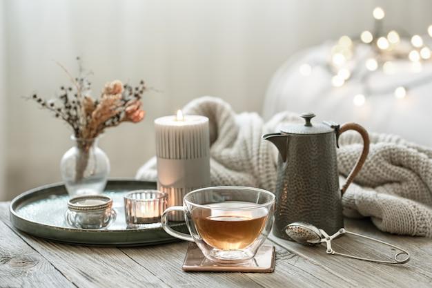 Gemütliches stillleben mit einer glastasse tee, einer teekanne und kerzen