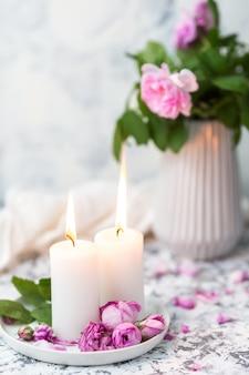 Gemütliches stillleben mit kerzen und rosa rosen auf einer weißen tabelle