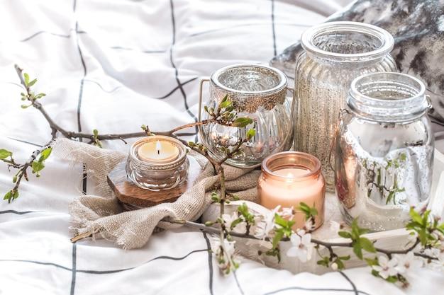 Gemütliches stillleben mit verschiedenen kerzen im bett