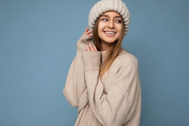 Gemütliches süßes foto einer schönen, glücklich lächelnden jungen dunkelblonden weiblichen person, die über einer blauen hintergrundwand isoliert ist und einen warmen pullover und eine strickmütze trägt, die zur seite schauen. freiraum