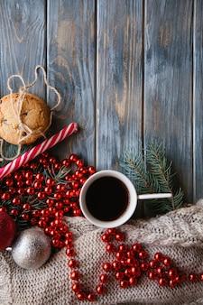 Gemütliches warmes urlaubsdekor auf holzhintergrund. weihnachtsstimmung und festliche stimmung. strickpullover und rote perlenschnur mit einer tasse heißem kaffee und schokoladenkeksen.