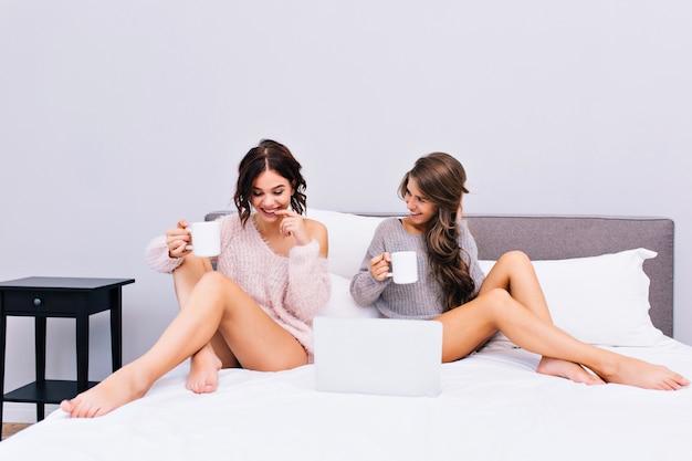 Gemütliches weiches bild von zwei jungen frauen in warmen wollpullovern, die auf bett in der modernen wohnung abkühlen. freudige mädchen trinken kaffee, kommunizieren, haben spaß zusammen. freunde, entspann dich, guten morgen.