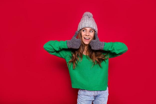 Gemütliches winterferienzeitporträt der entzückenden jungen dame, die grünen pullover und wintermütze trägt, die neues jahr feiert und siegeszeichen zeigt.