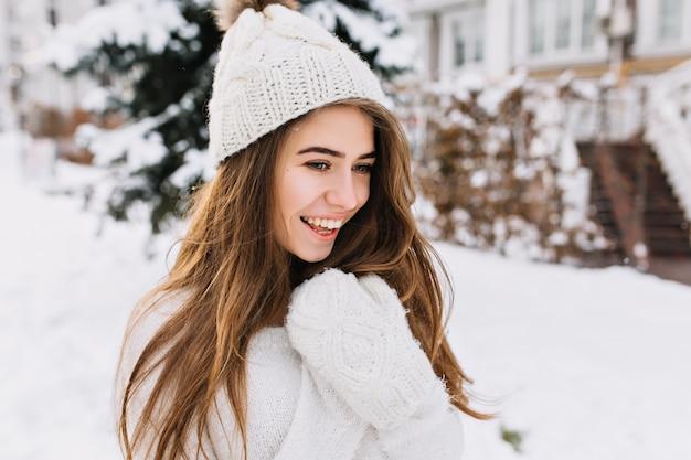 Gemütliches winterporträt der modischen freudigen jungen frau mit dem langen brünetten haar, das auf straße voll mit schnee geht. überrascht echte positive emotionen, warmweiße wollhandschuhe, strickmütze.