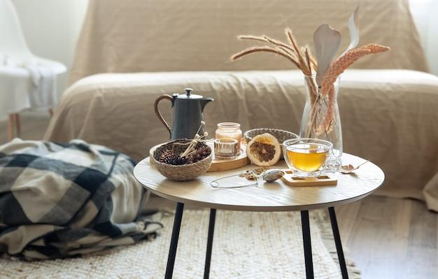 Gemütliches wohnstilleben mit einer tasse tee, kürbissen, kerzen und details der herbstdekoration auf einem tisch auf unscharfem hintergrund.