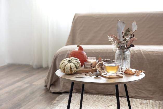 Gemütliches wohnstilleben mit einer tasse tee, kürbissen, kerzen und herbstdekordetails auf einem tisch auf einem unscharfen hintergrund des raumes.