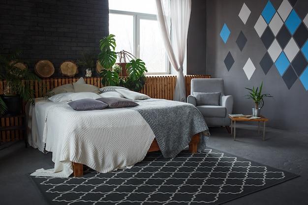 Gemütliches wohnzimmer des stilvollen dachbodens mit doppelbett, lehnsessel