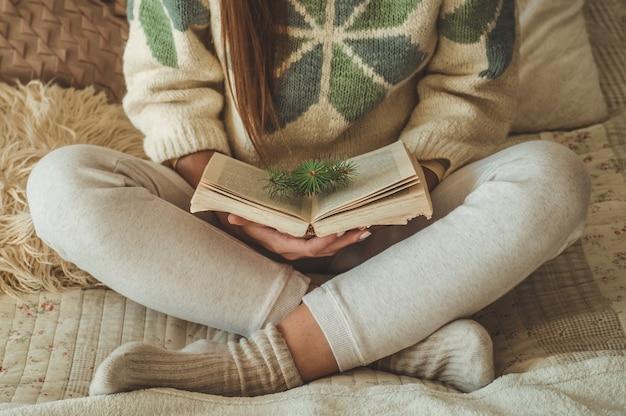 Gemütliches zu hause. schöne frau liest ein buch auf dem bett. guten morgen mit tee und buch. hübsche junge frau, die sich entspannt. das konzept des lesens
