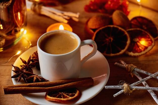 Gemütliches zu hause. tasse kaffee mit festlichen dekorationen und feenhaften girlandenlichtern