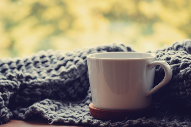 Gemütliches zuhause am herbsttag. wollschal und tasse tee auf dem fensterbrett