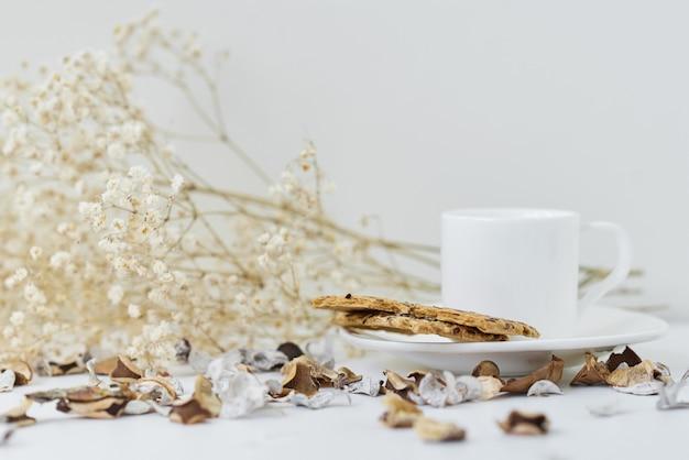Gemütliches zuhause mit einer tasse kaffee- und blumenzweig