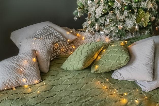 Gemütliches zuhause mit girlanden beleuchteten kissen, die in der nähe des reich verzierten weihnachtsbaums verstreut sind