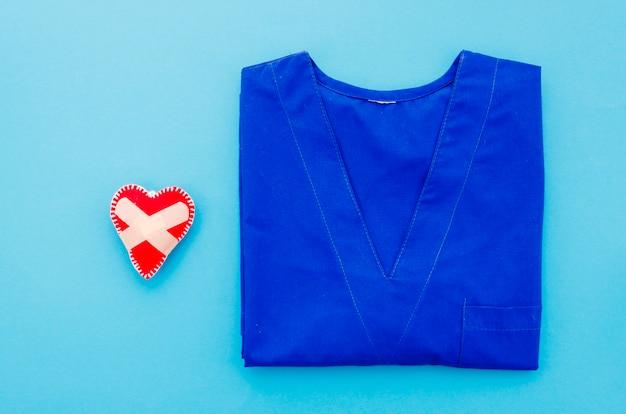 Genähtes herz mit selbstklebendem verband nahe dem medizinischen kleid auf blauem hintergrund