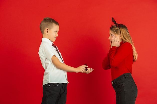 Genau wie ein erwachsener. valentinstagfeier, glückliche, niedliche kaukasische kinder lokalisiert auf rotem studiohintergrund. konzept der menschlichen gefühle, gesichtsausdruck, liebe, beziehungen, romantische feiertage.