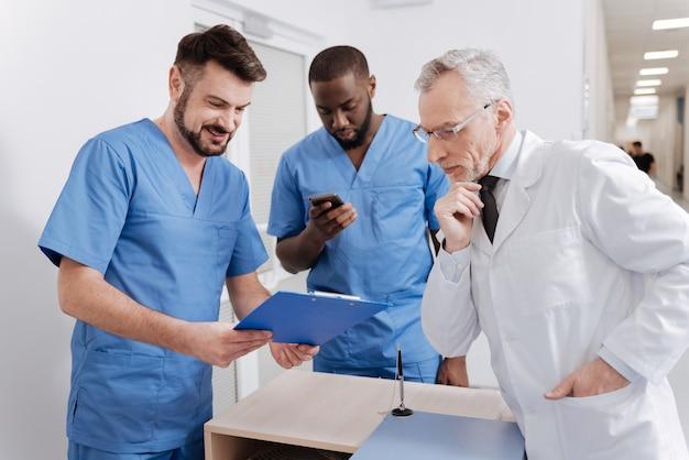 Genaue details angeben. beteiligter kluger alter mentor, der im krankenhaus arbeitet und den täglichen bericht überprüft, während er sich mit praktikanten unterhält