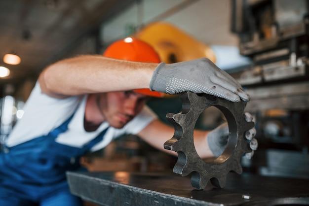 Genauigkeit erforderlich. mann in uniform arbeitet an der produktion. industrielle moderne technologie.