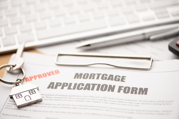 Genehmigter hypothekendarlehensvertragsantrag mit hausförmigem schlüsselring in nahaufnahme