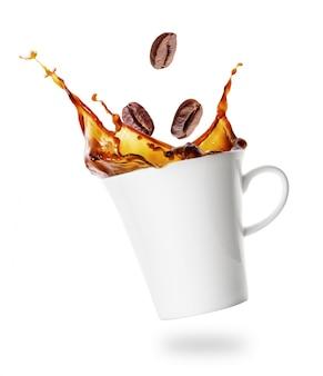 Geneigte tasse kaffee mit spritzer von fallenden körnern