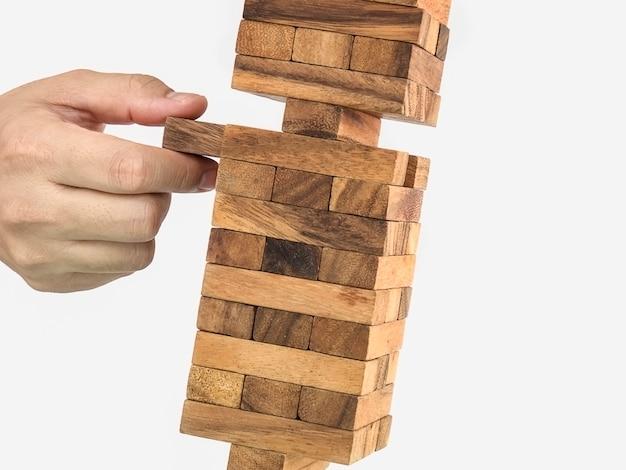 Geneigtes holzklotzturm jenga-spiel mit der hand, risikokonzept
