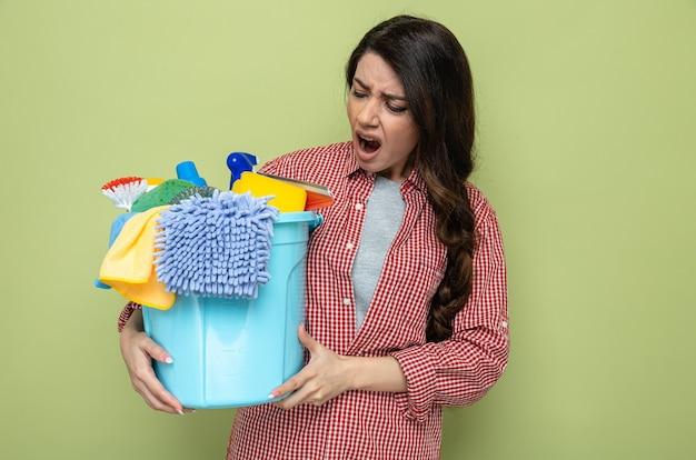 Genervte hübsche kaukasische putzfrau, die reinigungsgeräte hält und anschaut