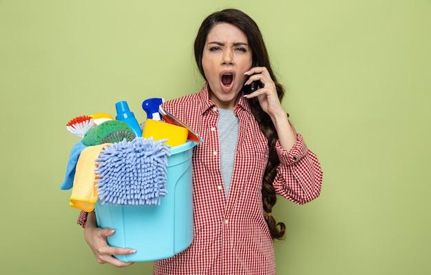 Genervte hübsche kaukasische putzfrau, die reinigungsgeräte hält und jemanden am telefon anschreit
