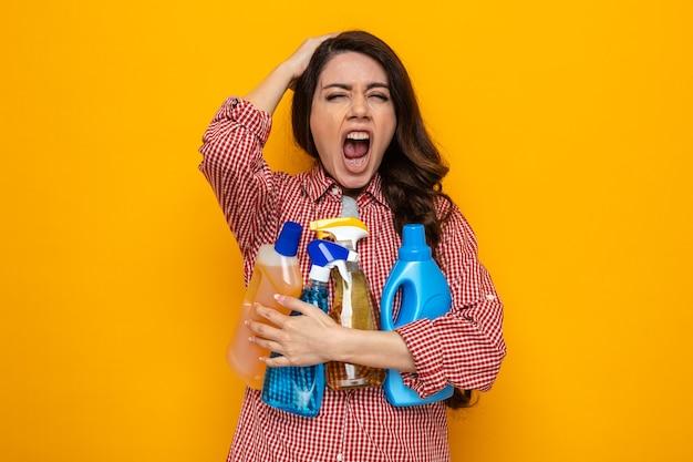 Genervte hübsche kaukasische putzfrau, die reinigungssprays und -flüssigkeiten hält und sich die hand auf den kopf legt