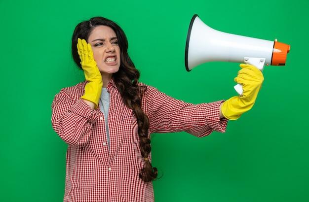 Genervte hübsche kaukasische putzfrau mit gummihandschuhen, die den lautsprecher hält und anschaut und die hand auf ihr gesicht legt