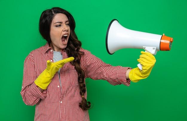 Genervte hübsche kaukasische putzfrau mit gummihandschuhen, die den lautsprecher hält und anschaut und die hand offen hält