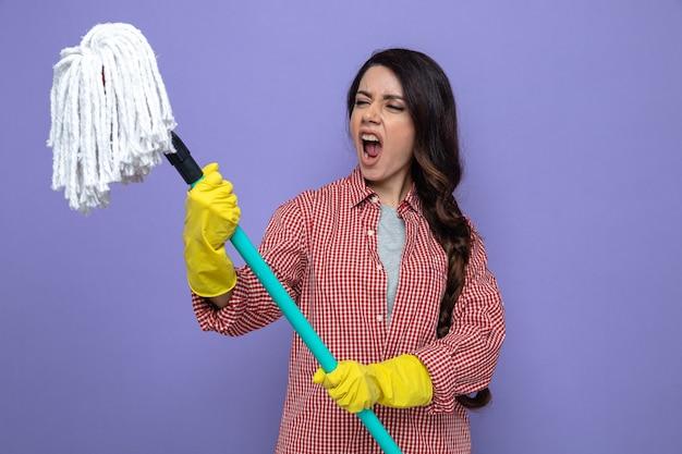 Genervte hübsche kaukasische putzfrau mit gummihandschuhen, die mop hält und betrachtet