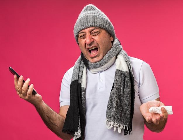 Genervter erwachsener kranker kaukasischer mann mit schal um hals, der wintermütze hält telefon und serviette lokalisiert auf rosa wand mit kopienraum